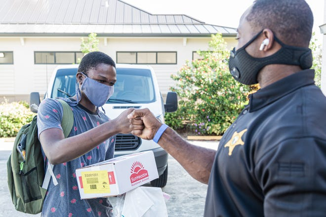 Clark Merilien, 17, who attends William T. Dwyer High School, fist-bumps Palm Beach County Sheriff's Deputy Anthony Dukes after receiving a backpack of school supplies and a box of non-perishable food at the Colony Youth Center in Palm Beach Gardens, last August.
