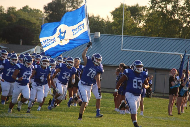 Perry football players run onto Dewey Field during the season opener. Perry will take on Winterset on Friday, Sept. 25 for homecoming.