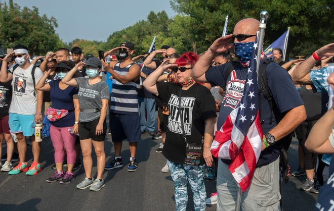 "Dozens from the community salute as they part in a Walk 9 Miles for the 9 Heroes event honoring Stockton's Christopher ""Bobby"" Gnem and the eight others who died during a training mission aboard a Marine amphibious assault vehicle that sank off the Southern California coast."