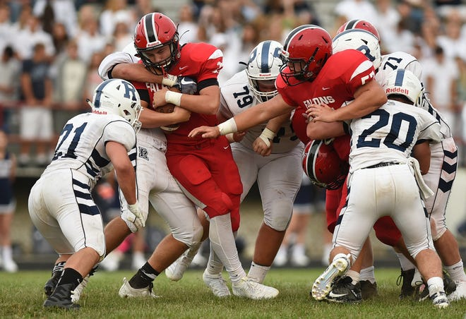 In this August 30, 2019 photo, Brimfield- Field football hosted Rootstown. Zack Davis holds on to the ball as Isaac Di Tirro gets the tackle. Dalton Duvall, Gaige McIntyre, Caleb Hillegas, Quiten White on the defensive play and Robert Atha for the Falcons. Lisa Scalfaro, Record-Courier