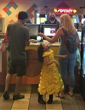 A little girl dances in her dressed-up duds as her parents purchase snacks prior to a Saturday afternoon matinee at Regal Valley River Center in Eugene.