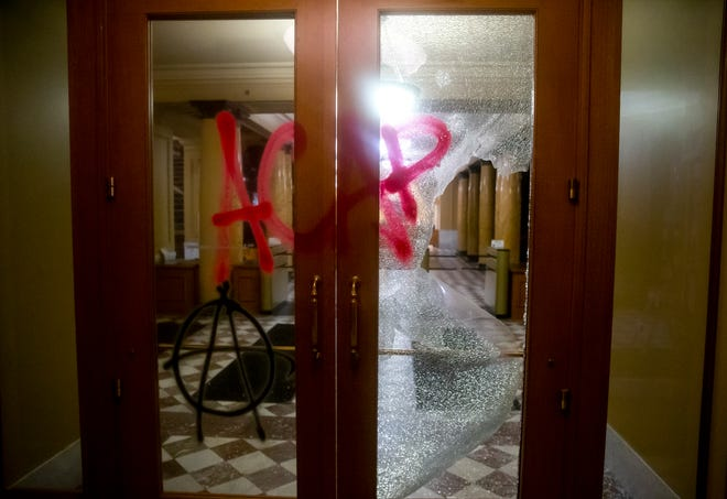 Graffiti is sprayed on a damaged door at City Hall in Portland on Tuesday. Officials say protesters in Portland smashed windows at City Hall in a demonstration that started Tuesday night and stretched into Wednesday morning.