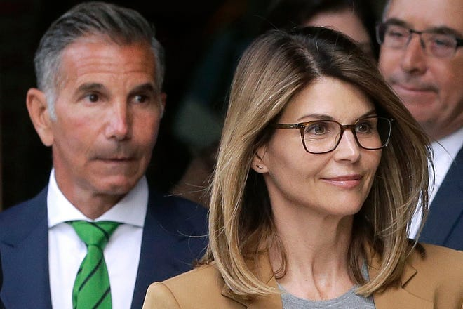 In this April 3, 2019, file photo, actress Lori Loughlin, front, and husband, clothing designer Mossimo Giannulli, left, depart federal court in Boston after facing charges in a nationwide college admissions bribery scandal.