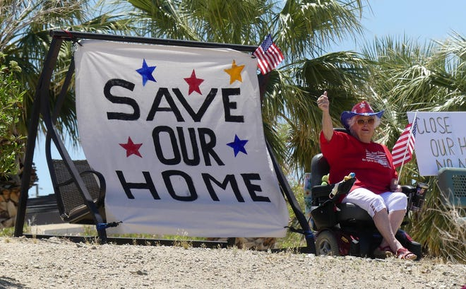 A resident at the Veterans Home of California-Barstow waves to a procession of nearly 1,000 vehicles passing by the facility on Memorial Day, May 25, 2020.
