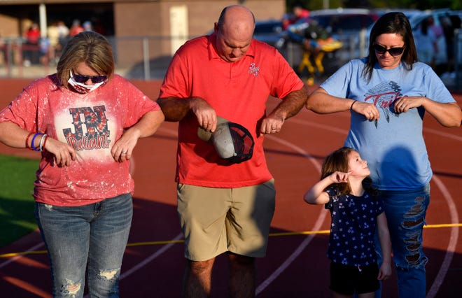 Jim Ned Indians supporters touch elbows in lieu of holding hands during a brief prayer for their team and the Ballinger Bearcats before Friday's game in Tuscola. Fans were encouraged to follow COVID-19 precautions at Indian Stadium.