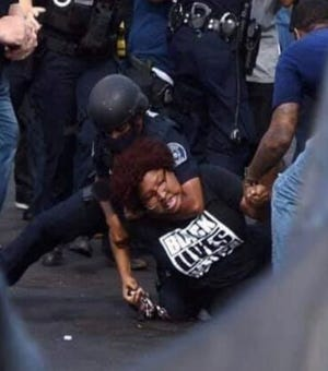 Information with this image from page 35 of a lawsuit, filed in U.S. District Court against Detroit police on Monday, claims an officer grabbed protester Nakia-Renee Wallace from behind and slammed her to the ground, placing her in a chokehold.