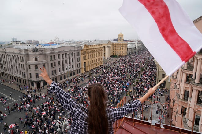A woman waves an old Belarusian national flag standing on the roof as Belarusian opposition supporters march to Independence Square in Minsk, Belarus, Sunday, Aug. 23, 2020.