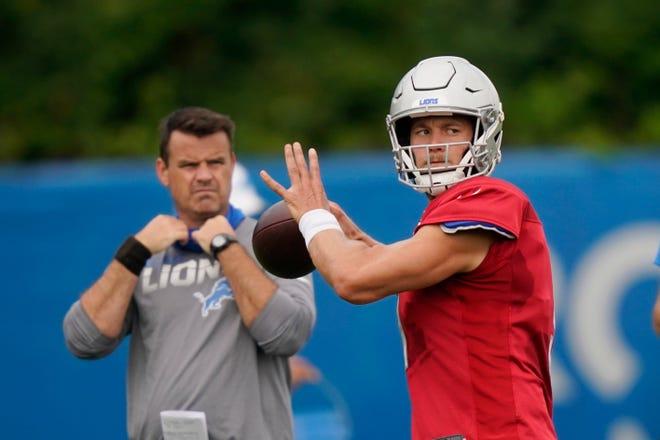 Quarterback Detroit Lions, Matthew Stafford, melempar saat pelatih quarterback Sean Ryan mengawasi.