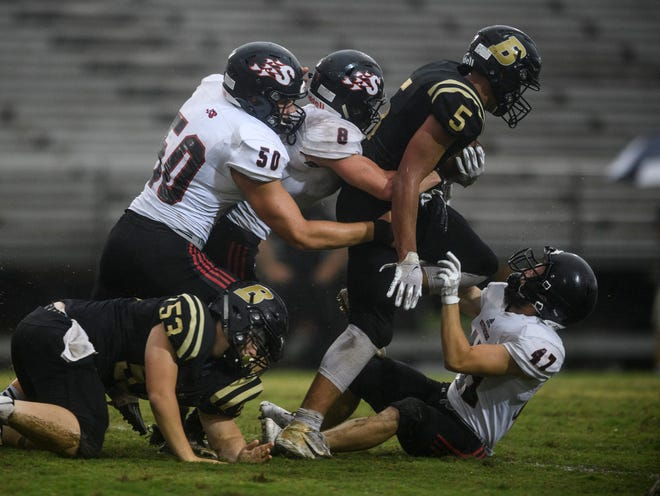Boonville's Devin Mockobee (5) is taking down by a sea of Southridge Raiders defensemen during the second quarter at Boonville High School in Boonville, Ind., Friday, Aug. 28, 2020.