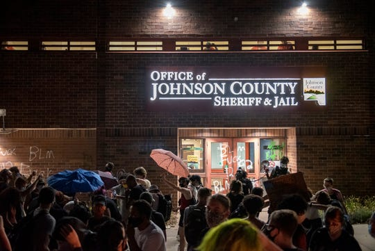 Protestors gather in front of the Johnson County Sheriff building during a protest for racial justice in Iowa City on Friday, August 28, 2020 .