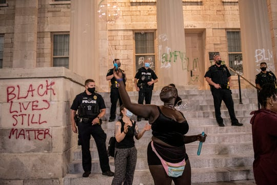 A protestor blows bubbles in front of police on the steps of the Old Capitol during a protest for racial justice in Iowa City on Friday, August 28, 2020 .