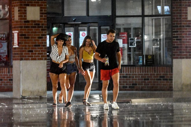 A group of people cross M.A.C Avenue in downtown East Lansing during a rainstorm on Friday, Aug. 28, 2020, during MSU's welcome weekend.