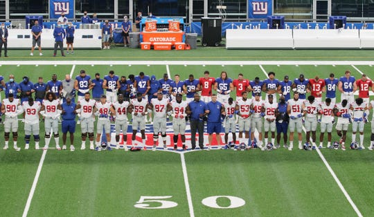 The NY Giants at midfield linking arms in a call for social justice before the New York Giants play an inter-sqaud game, the Blue White scrimmage at MetLife Stadium on August 28 2020.
