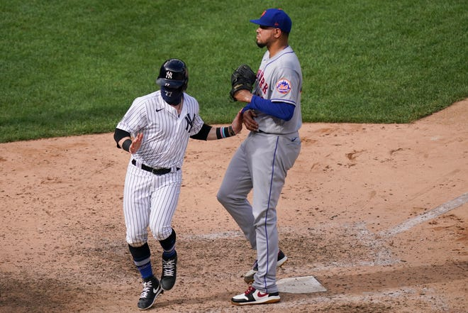 New York Yankees' Clint Frazier, left, scores the game-winning run on a wild pitch by New York Mets relief pitcher Dellin Betances, right, to close the ninth inning of a baseball game, Saturday, Aug. 29, 2020, in New York. The Yankees won 2-1. (AP Photo/John Minchillo)