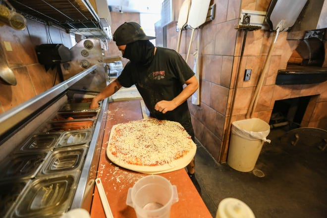Wade McDonald, owner of King Zah's Pizzeria in Las Cruces, makes a pizza for some of their first dine-in customers since their lobby opened after state-wide restriction were lifted on Saturday, August 29, 2020.