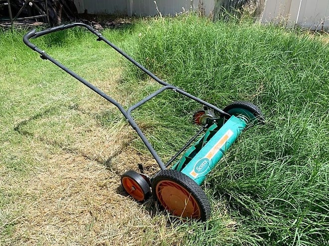 A human-powered lawn mower rests in a back yard in Deming, N.M. on Saturday, Aug. 29, 2020.
