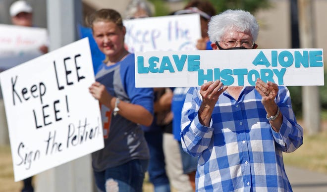 Demonstrators hold up signs protesting against changing the name of Lee Middle School in San Angelo on Saturday, Aug. 29, 2020.