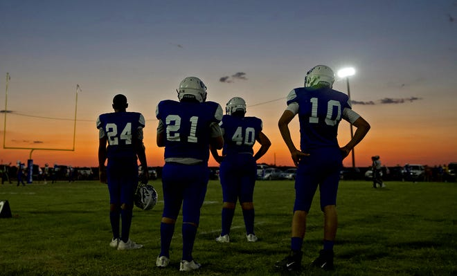 Members of the Olfen High School football team watch their teammates play in the first varsity game in the school's history Friday, Aug. 28, 2020.