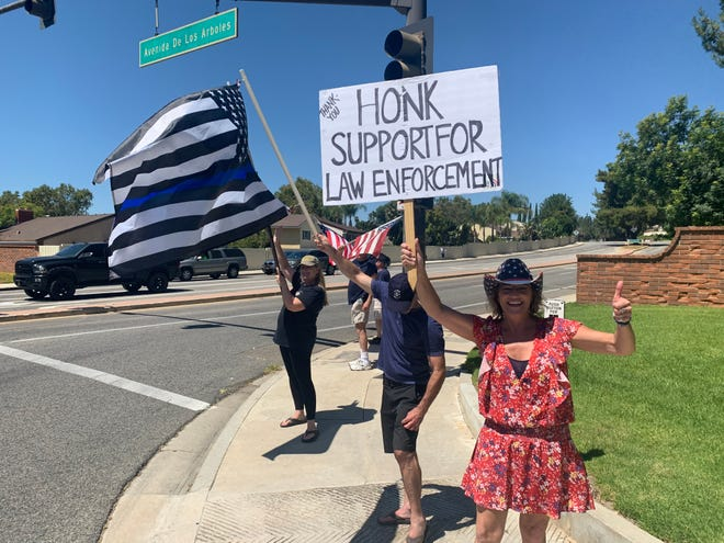 Gina Libby, right, encouraging passing motorists at the corner of Erbes Road and Avenida de Los Arboles in Thousand Oaks to honk their support for law enforcement on Saturday, Aug. 29, 2020.