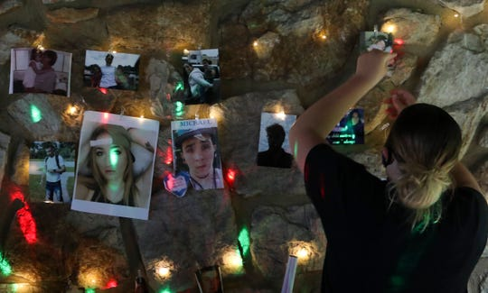 """Attendees place photos of loved ones lost to addiction in a temporary memorial during an """"Overdose Awareness"""" event at Banning Park Friday."""