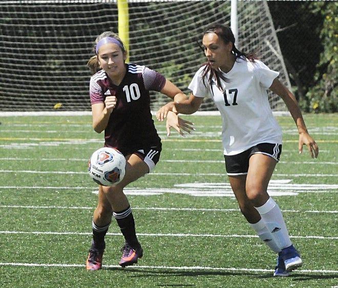 John Glenn's Caroline Lee (10) attempts to take control of the ball before New Philadelphia's Chloe Wing (17) during the girls soccer game on Saturday at John Glenn High School.