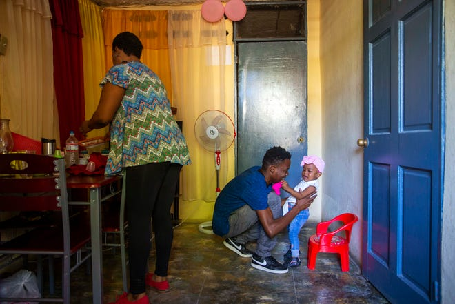 Verty plays with his 1-year-old daughter while his wife Saint Jean fixes the house in Port-au-Prince, Haiti, Tuesday, Aug. 25, 2020. The Trump administration has sharply increased its use of hotels to detain immigrant children before expelling them from the United States during the coronavirus pandemic. Verty says government contractors at a hotel where he was detained gave his family, including his daughter, cups of ice to eat to pass temperature checks prior to their deportation flight, even though they had tested negative for COVID-19.