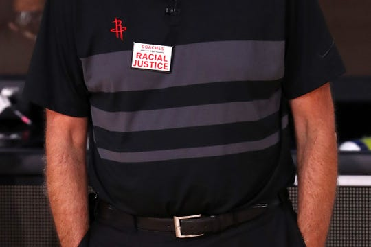 """Houston coach Mike D'Antoni wears a """"Coaches for Racial Justice"""" pin."""