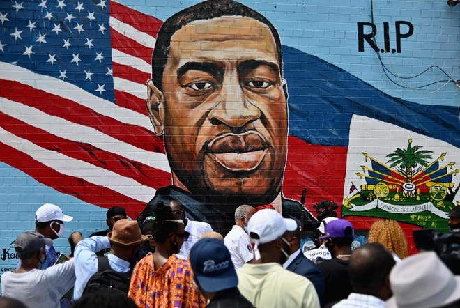 People gather at the unveiling in Brooklyn, N.Y., of artist Kenny Altidor's memorial portrait of George Floyd, who was killed on Memorial Day 2020 in Minneapolis with police officer Derek Chauvin kneeling on his neck for more than eight minutes.