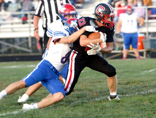 Crestview's Evan Hamilton (23) is tackled by Mapleton's Beau Galbraith (8) during high school football action on Saturday at Crestview High School. The Cougars won, 48-14.