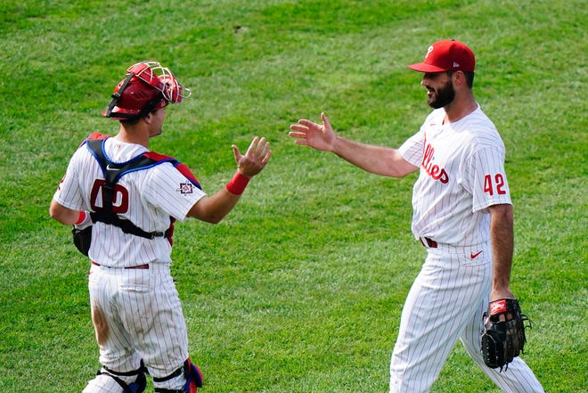 Phillies closer Brandon Workman, right, and catcher Andrew Knapp celebrate Saturday's 4-1 win over the Braves.