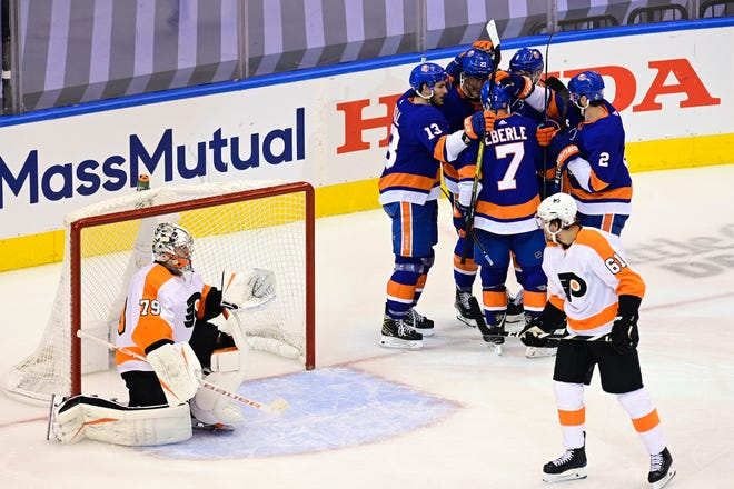 Islanders left wing Anders Lee. 27, and teammates celebrate his third-period goal as Flyers goaltender Carter Hart and defenseman Justin Braun look on during Game 3 on Saturday night.