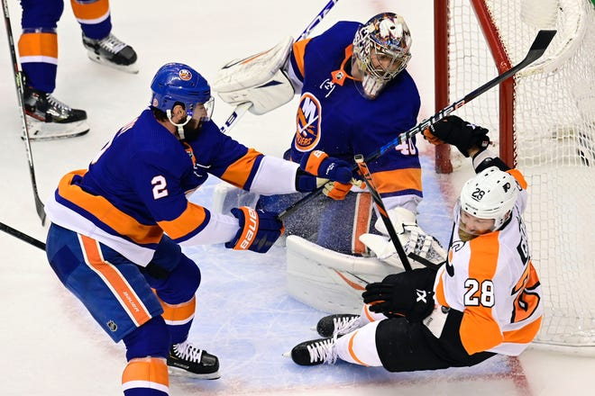 Islanders goalie Semyon Varlamov covers the side of the net as teammate Nick Leddy knocks Flyers captain Claude Giroux off of his feet during Game 3 on Saturday night.