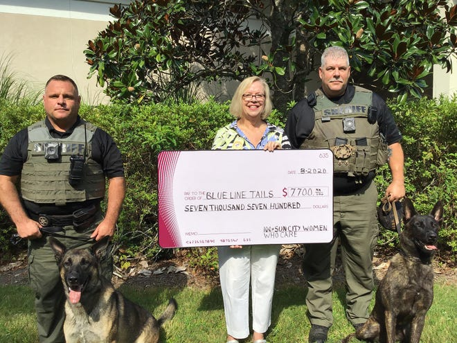 Vicki Mack of 100+ Sun City Women Who Care presents a donation to deputies Michael Messer, right, and Brock Tomlin, left, of Blue Line Tails. Their dogs are K-9 Bear, left, and K-9 Grim.