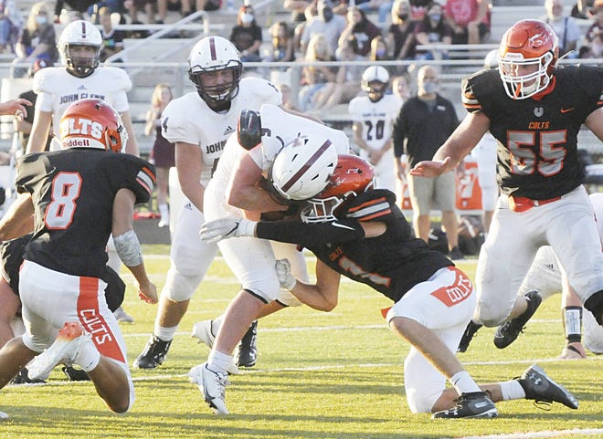 Meadowbrook's Hunter Eubanks (1) tackles John Glenn's Noah Wellmeier (6) during action Saturday evening at Meadowbrook High School. The Colts would hold on for a hard-earned 20-13 win in the season opener for both teams.