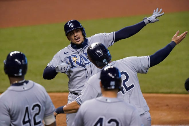 Tampa Bay Rays' Willy Adames, rear, celebrates with teammates after he hit a grand slam, also scoring Ji-Man Choi, Yandy Diaz and Yoshitomo Tsutsugo, during the fifth inning against the Miami Marlins on Sunday in Miami.