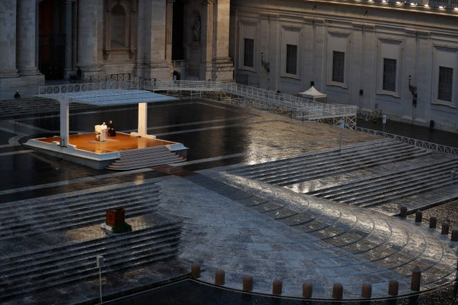 Pope Francis, white figure standing alone at center, delivers an Urbi et orbi prayer in March from the empty St. Peter's Square, at the Vatican.