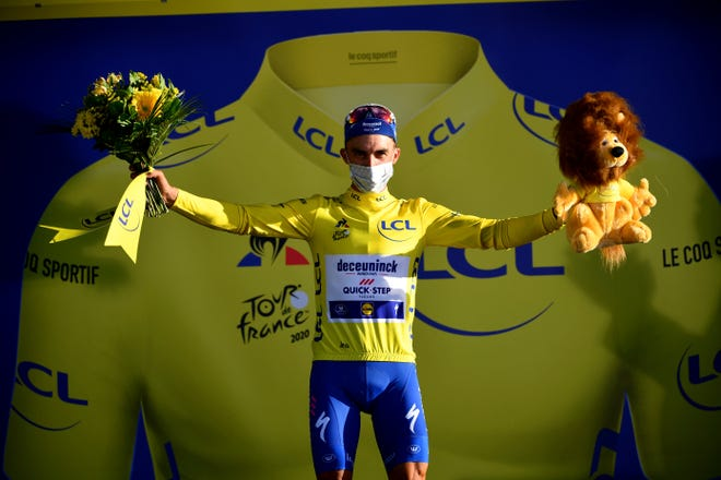 France's Julian Alaphilippe, wearing the overall leader's yellow jersey celebrates on podium after winning the second stage of the Tour de France cycling race Sunday.