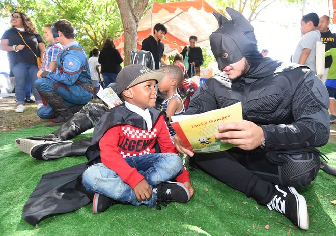"""Joshua Thompson, 5, is captivated by """"Batman,"""" aka Zeeshan Khan, as the superhero reads to him at the 22nd Annual Family Day at the Park in 2019. This year's signature literacy event will be virtual, 60 days long, and packed with online activities for families."""