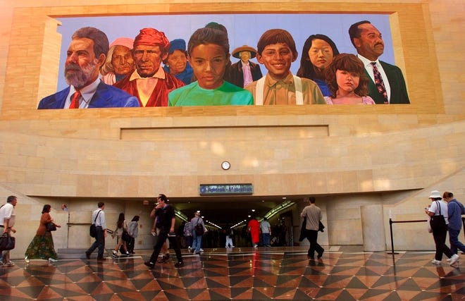 "Commuters walk into a tunnel at Los Angeles' Amtrack-Metrolink Union Station under the mural ""City of Dreams/River of History"" by artist Richard Wyatt, showing the diversity of California's population, in 2000. California moved closer Saturday to requiring corporate boards to include racial or sexual minorities, expanding on a new law that sets a similar requirement for including women directors. The diversity bill approved by the Senate would require California-based public corporations to have one board director from an underrepresented community by the end of 2021."