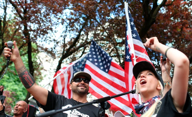 Joey Gibson, left, leader of Patriot Prayer, participates in the group's rally in Portland on June 30, 2018.