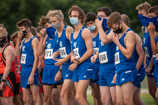 Harper Creek cross country runners wear face masks at the starting line of the Optimist Invitational on Saturday, Aug. 29, 2020 at Harper Creek High School in Battle Creek, Mich.