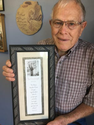 Herman Luhring of Parkersburg, whose wife Shirley was killed in a May 25, 2008, tornado that ravaged the city, holds a Bible verse -- Jeremiah 29:11 -- that hangs in his rebuilt home, which gives him hope. He still takes regulated medication for injuries suffered in the tornado.