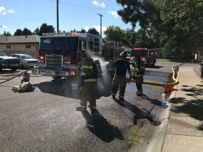 Firefighters with Great Falls Fire Rescue hose off contaminants after battling an apartment fire on the east end of Great Falls Sunday.