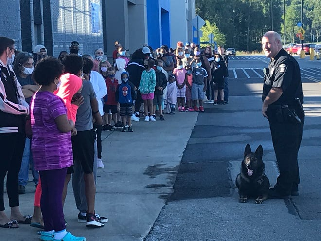 Mansfield police Officer Jake Rietschlin and his K9 Mekel greet the 110 children and teens who were part of the  Mansfield FOP Lodge 32 Cops N Kids shopping event Sunday morning at Walmart on Possum Run Road.