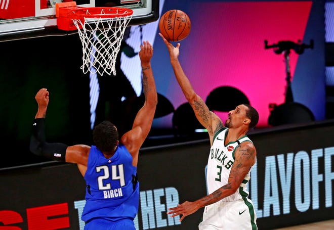 Bucks guard George Hill beats Magic forward Khem Birch for a layup in the fourth quarter Saturday.