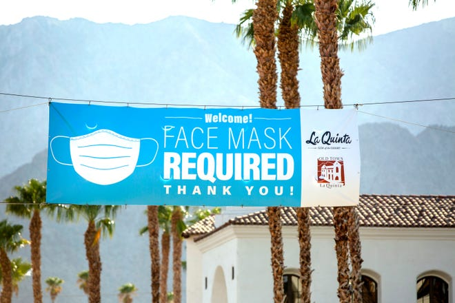 A Face Mask Required banner is displayed in Old Town La Quinta, Calif., on August 27, 2020, amid the coronavirus pandemic.