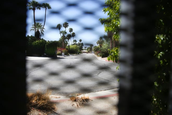 The El Mirador neighborhood can be seen through a gate that intersects Fiesta Road in Palm Springs, Calif. on Sunday, August 30, 2020.