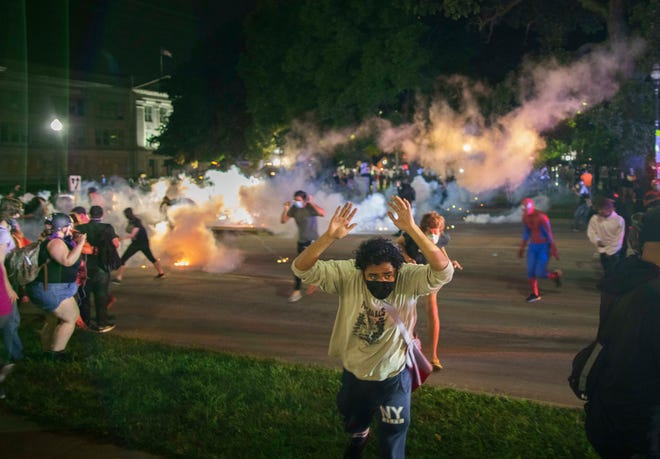Tear gas lands around protesters after they refused to listen to police demands to disperse near the courthouse in Kenosha, Wisconsin on Tuesday, August 25, 2020. (Chris Juhn/Zuma Press/TNS)