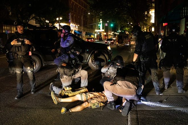ADDS THE SHOOTING WAS FATAL - A man is treated after being shot Saturday, Aug. 29, 2020, in Portland, Ore. It wasn't clear if the fatal shooting late Saturday was linked to fights that broke out as a caravan of about 600 vehicles was confronted by counterdemonstrators in the city's downtown.