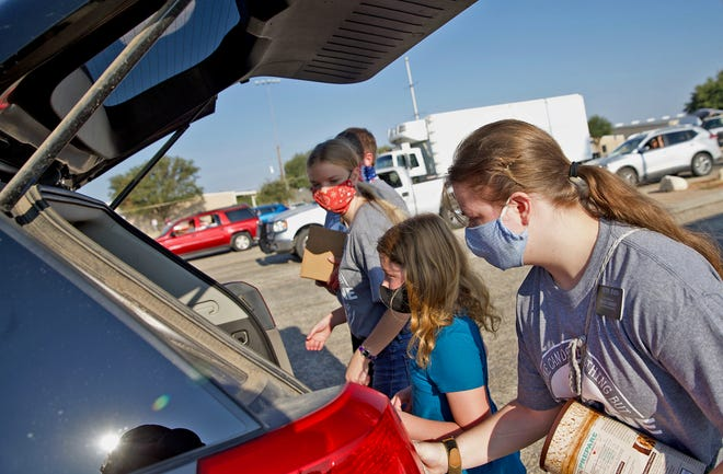 Volunteers load items into a vehicle during a food drive held by the Concho Valley Regional Food Bank in the Foster Communications Coliseum parking lot Saturday, Aug. 29, 2020.